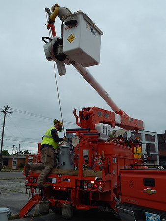 CATHY SPAULDING/Muskogee Phoenix<br /> OG&E lineman Mike Knupp, bottom, attaches a cable to a transformer while lineman Kevin Luper holds the cable from his bucket. An OG&E crew replaced the transformer that controlled the traffic light at Main and Court streets. The light, which had not been working, was functional by late Thursday morning.