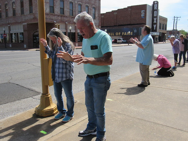 CATHY SPAULDING/Muskogee Phoenix Wanda and Charles Branham, left, join in a Saturday morning prayer gathering in downtown Muskogee. Several dozen people lined up along Okmulgee Avenue in front of the Muskogee Municipal Building and city parking lot to pray for the city. Participants stood on pieces of tape spaced several feet apart. The Praying for Muskogee gathering was organized by Jordan Howard, pastor of Jubilee Christian Center.