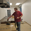 CATHY SPAULDING/Muskogee Phoenix<br /> Jesse Ashwood of Able Plumbing cleans up after working on the new kitchen in Muskogee Church of Christ's fellowship hall addition. The addition is about 90 percent finished.