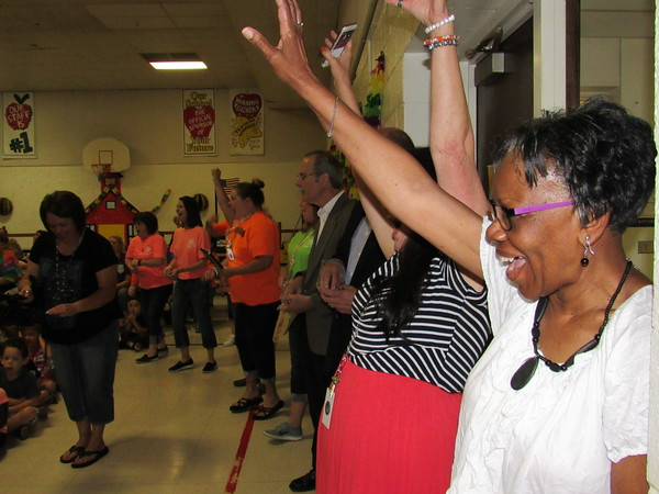 Staff photo by Cathy Spaulding<br /> Early Childhood Center office assistant Bernita Wallace, right, joins other staff members in celebrating the announcement. Muskogee Superintendent Mike Garde, center, joins the festivities.