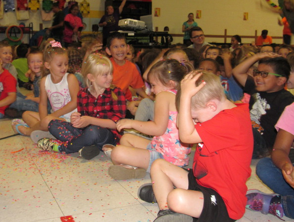 """Staff photo by Cathy Spaulding<br /> Early Childhood Center pupils shield themselves from confetti thrown Tuesday morning at a """"watch party"""" where the school was named a National School of Character."""