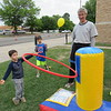 CATHY SPAULDING/Muskogee Phoenix<br /> Josh Foster, 3, almost tosses a hula hoop over a peg while brother Benjamin Foster, 6, and David Lester watch during the Faster Than the Pastor block party on Friday. First Baptist Church and Timothy Baptist Church got together to host the block party and foot races at First Baptist Church. The event had been postponed from the week before. It featured inflated games, free food and a petting zoo.