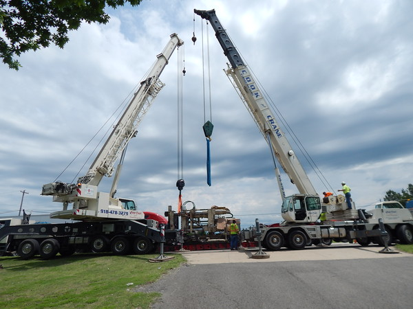 Staff photo by Mark Hughes<br /> Cranes prepare to lift a 153,000-pound machine from a tractor-trailer rig Wednesday. The rig experienced mechanical failure on U.S. 69. The cranes unloaded the trailer to allow it to be repaired. The machine was set down at the city of Muskogee's visitors center.