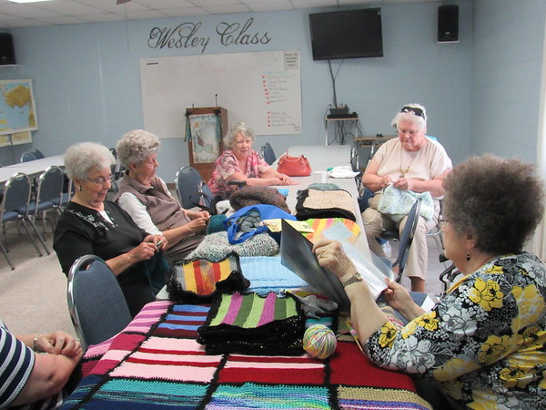 Staff photo by Cathy Spaulding<br /> Participants in the First United Methodist Church Prayer Shawl Ministry — from left, Phyllis Feagans, Carolyn Thompson, Deanna Dean, Karen Cookson (obscured), Linda Clark and Sondra Harris — meet once a month to make shawls, blankets and caps.