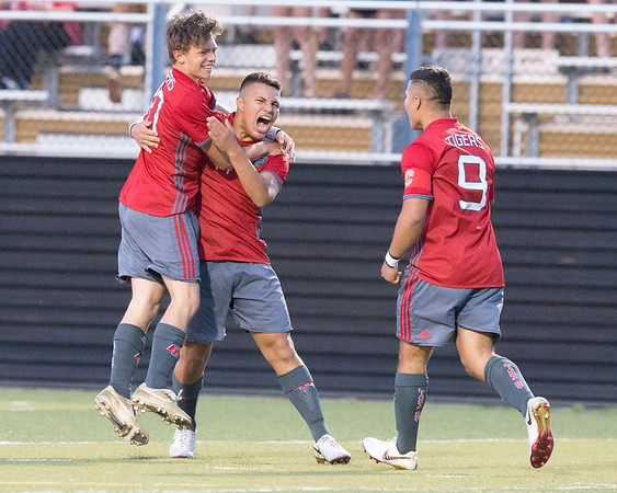 VON CASTOR/Special to the Phoenix<br /> Fort Gibson's Jose Estrada celebrates with teammates Grayson Ramey, left, and Marcos Estrada, right, moments after scoring the first goal of the 4A championship game Friday night against Skiatook in Sand Springs. The Tigers won 2-0 for their second straight state title.