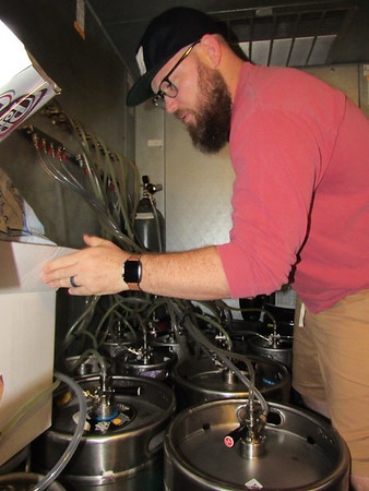 Jonathan Hawke inspects beer kegs at The Rail Taproom.