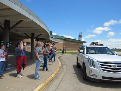 CATHY SPAULDING/Muskogee Phoenix Intermediate Elementary students poke out of a sport utility vehicle roof to wave to teachers on the final day of the school year Friday. They had to keep their distance out of concern for COVID-19.
