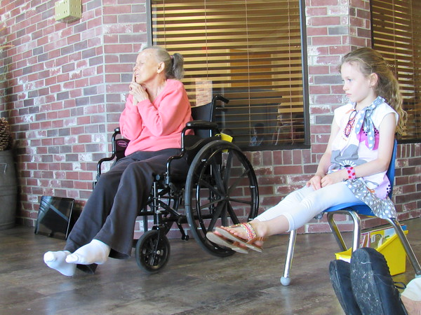 Staff photo by Cathy Spaulding<br /> Caroline Ormand, a resident at The Springs, joins Ben Franklin Science Academy kindergartner Gretchen Doughty in an ankle stretch during morning exercises. Gretchen attends class at the skilled nursing and care center.