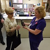 "Staff photo by Mark Hughes<br /> Donna Powell, left, presents a figurine, ""The Healing Touch,"" to Marji Schabitzer, a registered nurse at EASTAR Health System who received the DAISY Award on Thursday. Powell nominated Schabitzer for going ""above and beyond in caring for my husband,"" she said."