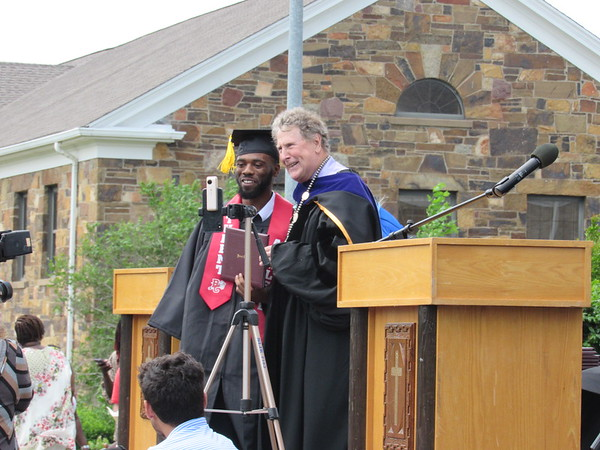 CATHY SPAULDING/Muskogee Phoenix<br /> Bacone College graduate Antonio Wilson receives his diploma from outgoing Bacone President Dr. Franklin Willis during commencement Saturday. Wilson said he thought about the prospect of being Bacone's final graduate.