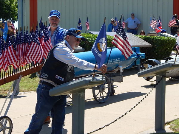 Staff photo by Mark Hughes<br /> Tom Hampton places a small American flag at one a stanchion representing one of 65 submarines that have been lost at sea. Sailors from a Navy detachment stationed at Tinker Air Force Base stand in the background.