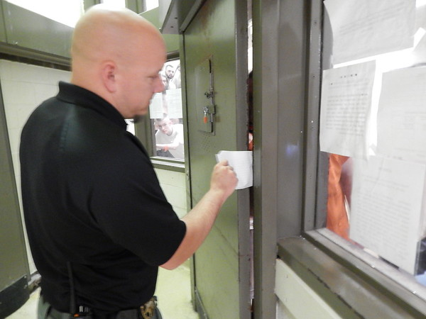 Staff photo by Wendy Burton<br /> An inmate slides a letter to Jail Administrator Jeremy Garvin as he guides a tour through Muskogee County/City Detention Center.