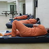 Staff photo by Wendy Burton<br /> Inmates recline on their beds in the day-room area of the pod to which they are assigned at the Muskogee County/City Detention Facility. The jail remains over capacity, but not by as much as it has been during the preceding year.