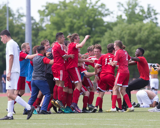 Phoenix special photo by Von Castor<br /> Fort Gibson's Grayson Ramey is mobbed by his teammates after converting a penalty kick in overtime to lift the Tigers by Santa Fe South 1-0 to capture the Class 4A boys soccer state championship Saturday at the University of Tulsa soccer and track complex.