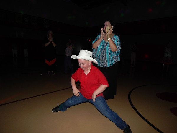 CATHY SPAULDING/Muskogee Phoenix<br /> Intermediate Elementary third-grader Ethan Mosteller gets into some splitting action while his mother, Andrea Mosteller, claps along during Friday's Mother Son dance at the IES.