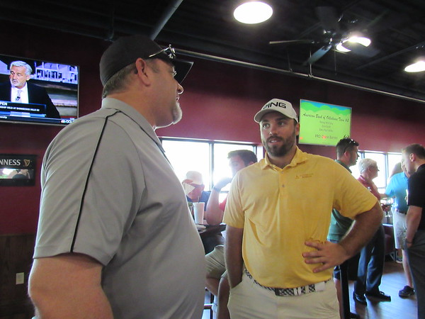 CATHY SPAULDING/Muskogee Phoenix Ron Morton of TTCU, left, visits with professional golfer Gregory Yates at an APT Pro Tour pairing party, held Monday night at Muskogee Golf Club. Yates will be paired with a TTCU team Tuesday.