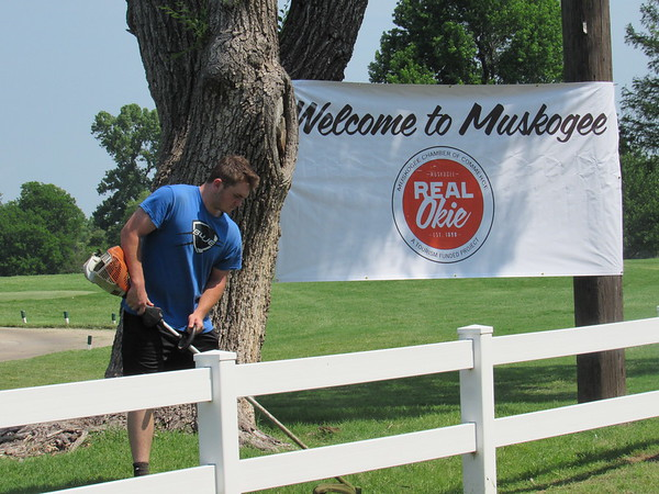 CATHY SPAULDING/Muskogee Phoenix Justin Garrett cuts grass by a Muskogee Chamber of Commerce welcome sign at Muskogee Golf Club. The club will host the APT Pro Tour this week, bringing up to $2.5 million in economic impact to Muskogee.