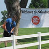 CATHY SPAULDING/Muskogee Phoenix<br /> Justin Garrett cuts grass by a Muskogee Chamber of Commerce welcome sign at Muskogee Golf Club. The club will host the APT Pro Tour this week, bringing up to $2.5 million in economic impact to Muskogee.