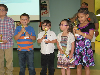 "CATHY SPAULDING/Muskogee Phoenix Pershing Elementary kindergarteners, from left, Jayse Boyd, P.J. Snow, Nevaeh Keeton and Eva Hall relish receiving trophies for placing first in the Muskogee Public Schools Drug-Free Video contest. They won with ""Hug a Pug."""