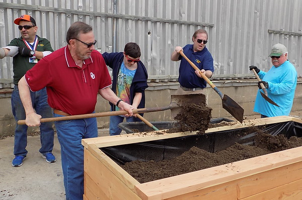 MIKE ELSWICK/Muskogee Phoenix<br /> Taylor Foster, executive director, second from right, said the garden produce will be used to provide healthier eating to<br /> employees and will be sold to residents to help raise money for the nonprofit.