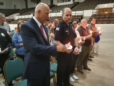 CHESLEY OXENDINE/Muskogee Phoenix Muskogee Police Department Deputy Chief Chad Farmer helps Chief Johnny Teehee light his vigil candle during a ceremony held Thursday for fallen police officers.