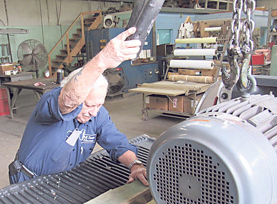 Ed Rivard loads a repaired motor onto a pickup bed. He has repaired machine motors since 1961.