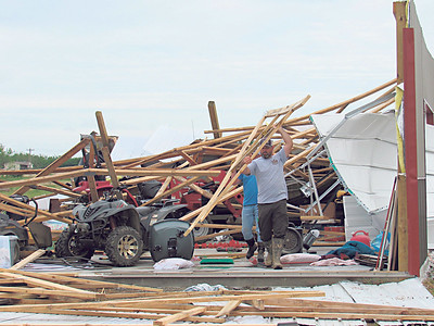 CATHY SPAULDING/Muskogee Phoenix David Fuller, left and Roy Parker carry a ceiling support from Parker's storage garage, which was destroyed in Friday storms.
