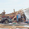 CATHY SPAULDING/Muskogee Phoenix<br /> David Fuller, left and Roy Parker carry a ceiling support from Parker's storage garage, which was destroyed in Friday storms.