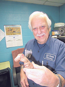 Ed Rivard shows off an animal-shaped paperweight he made with melted copper wire. He works a lot with copper wire at his machine motor repair shop.