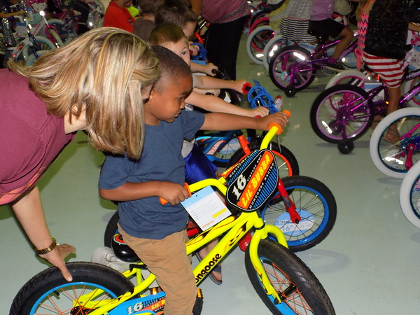 Special photo by Mike Elswick<br /> Mary White Elementary School pre-kindergarten teacher Terri Martin, left, visits with Keith Titsworth as he checks out his new bike Wednesday in the school gym.