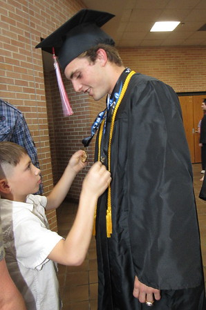 CATHY SPAULDING/Muskogee Phoenix Fort Gibson High School senior Carter Lawson lets his young cousin Karsyn Deckard study his medals before Friday night's Fort Gibson commencement. Lawson won the state championship medals in 2017 and 2018 for soccer.