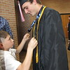 CATHY SPAULDING/Muskogee Phoenix<br /> Fort Gibson High School senior Carter Lawson lets his young cousin Karsyn Deckard study his medals before Friday night's Fort Gibson commencement. Lawson won the state championship medals in 2017 and 2018 for soccer.