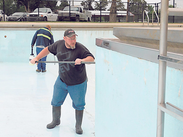 KENTON BROOKS/Muskogee Phoenix<br /> Justin Wiley of the Wagoner Parks and Recreation Department, right, scrubs down a wall in the Wagoner pool.