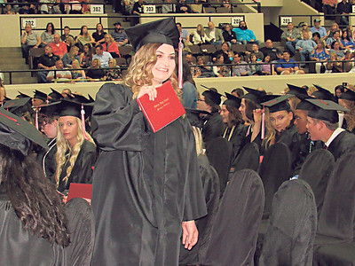 CATHY SPAULDING/Muskogee Phoenix Kylie Howell shows off a diploma designating her as a Hilldale High School graduate Saturday during Hilldale commencement ceremony.