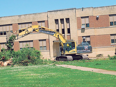 KENTON BROOKS/Muskogee Phoenix A backhoe from Manhattan Construction Co. of Tulsa tears down and clears away trees from the front of Alice Robertson Junior High School on Monday as work began to demolish the school, which opened in 1939. It will be replaced by a freshman academy.