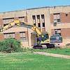 KENTON BROOKS/Muskogee Phoenix<br /> A backhoe from Manhattan Construction Co. of Tulsa tears down and clears away trees from the front of Alice Robertson Junior High School on Monday as work began to demolish the school, which opened in 1939. It will be replaced by a freshman academy.