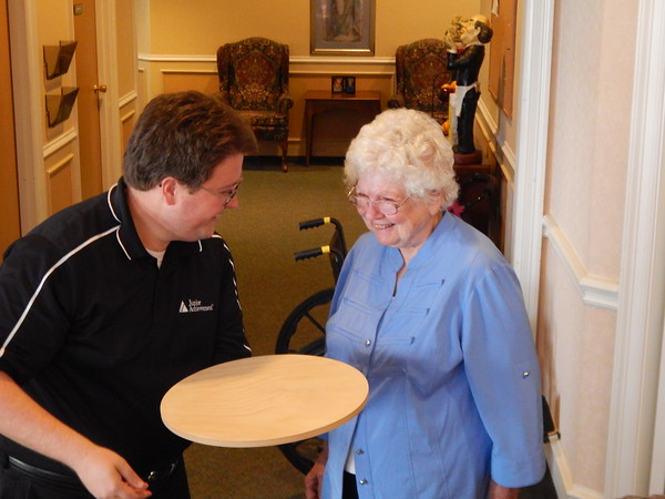 Staff photo by Mark Hughes<br /> Brian Jackson of Junior Achievement shows Thelma Whittinghill one of the 15 Lazy Susans made by the Muskogee High School carpentry class. Whittinghill, a resident at Country Gardens Assisted Living Community, asked for the rotating trays to make mealtime easier.