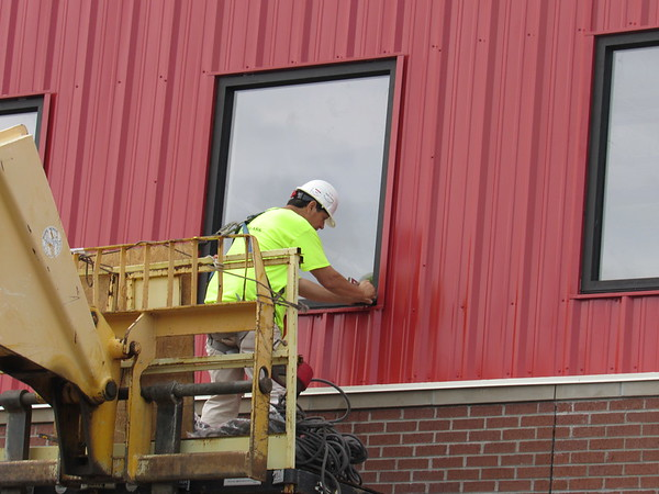 CATHY SPAULDING/Muskogee Phoenix<br /> A worker installs a seal around a window pane at Hilldale Elementary's new gym, which is under construction. A new Hilldale Elementary entrance and office area is to open by July, and a new gym and classroom addition, with a connecting hall, is to open by the start of the next school year in August, said Hilldale Superintendent Erik Puckett.