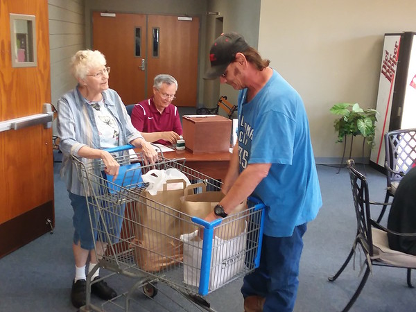 Staff photo by Mark Hughes<br /> Muskogee Community Food Pantry volunteer Shirley Reiner delivers two bags of food to Bryan Barefoot Wednesday at the Muskogee Community Food Pantry at First United Methodist Church.