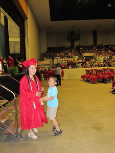 CATHY SPAULDING/Muskogee Phoenix Andy Jiang, 7, jumps to greet his big sister, Shuxian Jiang after received her diploma during Hilldale High School's commencement ceremony Saturday.