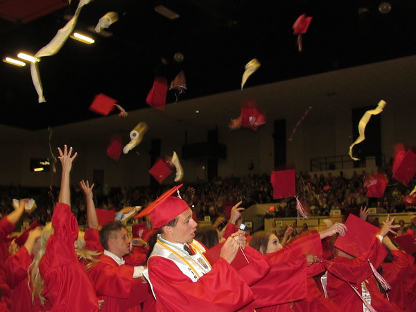 CATHY SPAULDING/Muskogee Phoenix<br /> Hilldale High School graduates toss mortar boards and other items into the air at the end of their commencement ceremony Saturday at Muskogee Civic Center. The ceremony was filled with joy and a few tears.