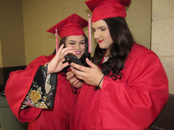 CATHY SPAULDING/Muskogee Phoenix<br /> Patricia Arnold, left, and Kiley Arnold look at a picture before they joined classmates in Hilldale High School's commencement ceremony Saturday afternoon. They have been friends since fourth grade.