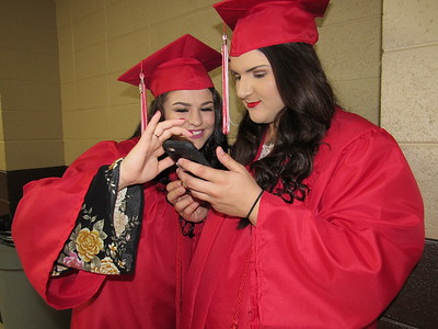CATHY SPAULDING/Muskogee Phoenix Patricia Arnold, left, and Kiley Arnold look at a picture before they joined classmates in Hilldale High School's commencement ceremony Saturday afternoon. They have been friends since fourth grade.
