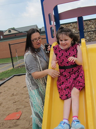 Marcella Bynum guides 7-year-old Genvieve Fitzgerald down a slide at Oklahoma School for the Blind. Bynum has been a direct care specialist at OSB since 2004.