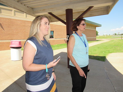 CATHY SPAULDING/Muskogee Phoenix Retiring Intermediate Elementary School Principal Sherry Rybolt, right, and her successor, Andrea Sifert, watch traffic after the end of a school day.