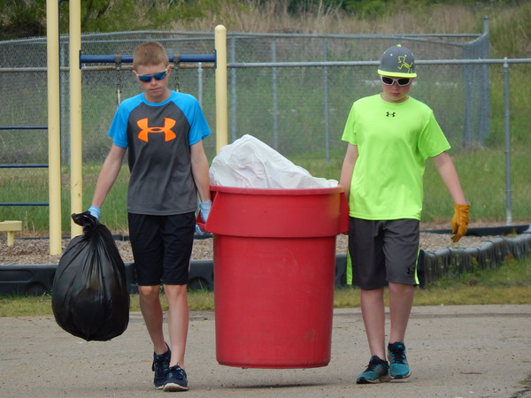 Staff photo by Mark Hughes<br /> Broc Fletcher and his brother, Boone, carry out trash collected during Saturday's cleanup at Hilldale Elementary School.