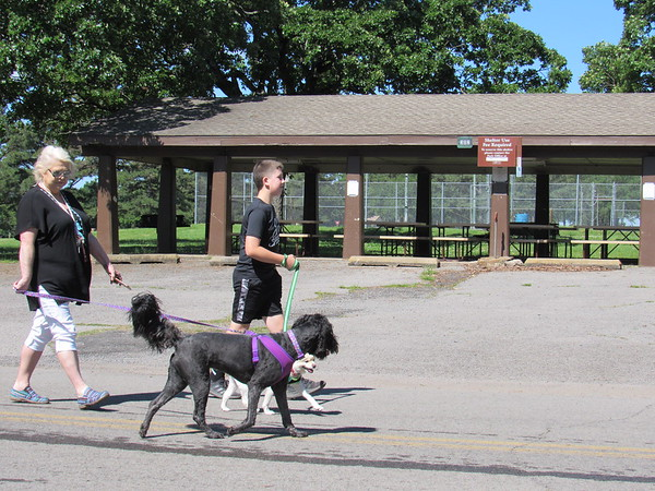 CATHY SPAULDING/Muskogee Phoenix<br /> Joan Hudson and her grandson, Hunter Jones, both of Coweta, walk their dogs, Darcy and Ozzy, by a Sequoyah Bay State Park pavilion Wednesday.