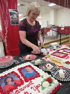 CATHY SPAULDING/Muskogee Phoenix Hilldale Elementary emergency medical technician Dorsinda Wiedel, who is retiring after 29 years at Hilldale, serves cake honoring school retirees.