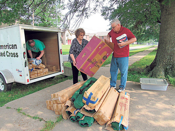 Red Cross volunteers, from left, Chris Gideon, Marcia Gideon and Robert Gideon take boxes of foam cups and portable cots from a trailer at a temporary shelter set up at Bacone College's old gym.
