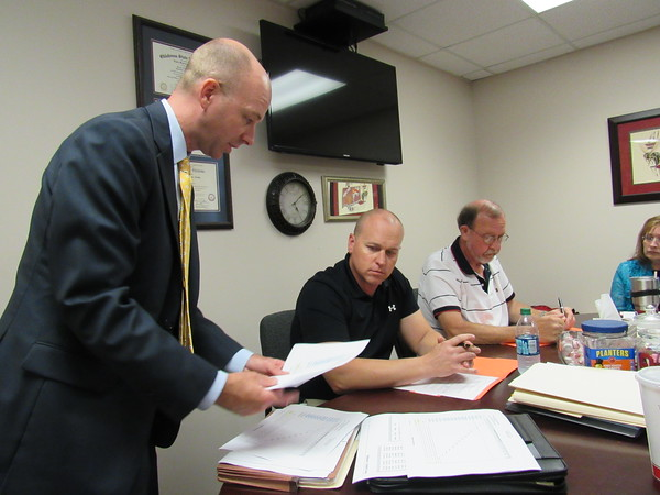 Staff photo by Cathy Spaulding<br /> Financial adviser Jordan Smith of Stephen L. Smith Corp., left, presents information about two proposed bond issues to the Hilldale school board, including President Derek Nunn, center, and Vice President Vernon Antonioni.
